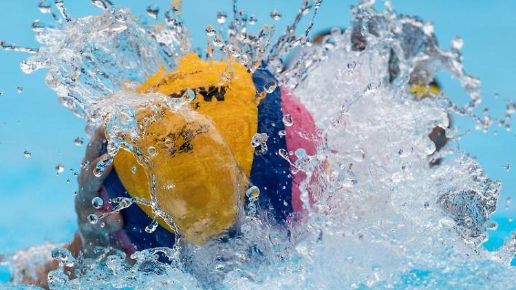 Ein Wasserball klatscht auf die Wasseroberfläche. Foto: Bernd Thissen/dpa/Archivbild
