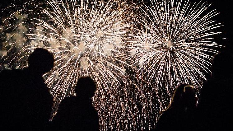 Besucher sehen sich ein Feuerwerk an. Foto: Christoph Schmidt/dpa/Archivbild