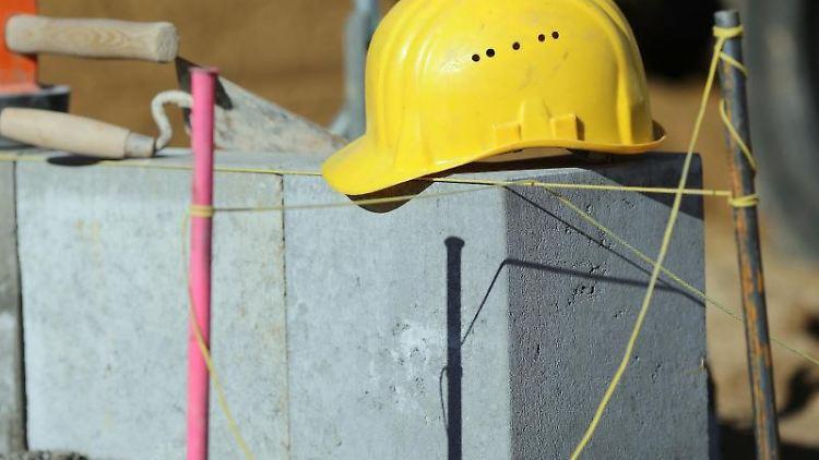 Ein gelber Bauarbeiterhelm liegt auf Mauerwerk auf einer Baustelle in Magdeburg. Foto: Jens Wolf/dpa-Zentralbild/dpa/Archivbild