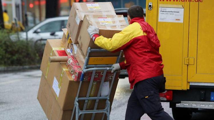 Ein Paketbote der Post schiebt eine Sackkarre mit Paketen über Straße. Foto: Malte Christians/dpa/Archivbild