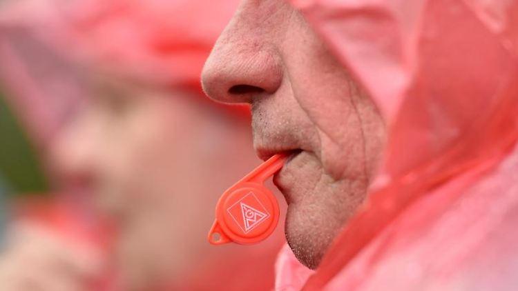 Ein Mann hat bei einer Kundgebung eine Trillerpfeife mit dem IG Metall Logo im Mund. Foto: Caroline Seidel/dpa/Archivbild