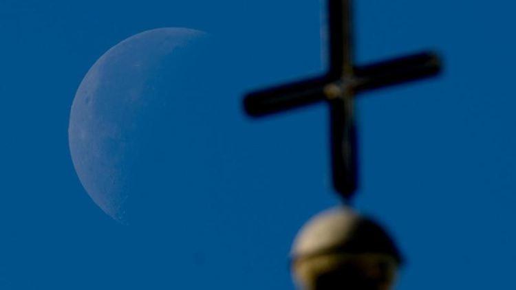 Der Mond ist hinter dem Kreuz eines Kirchturms zu sehen. Foto: Swen Pförtner/dpa