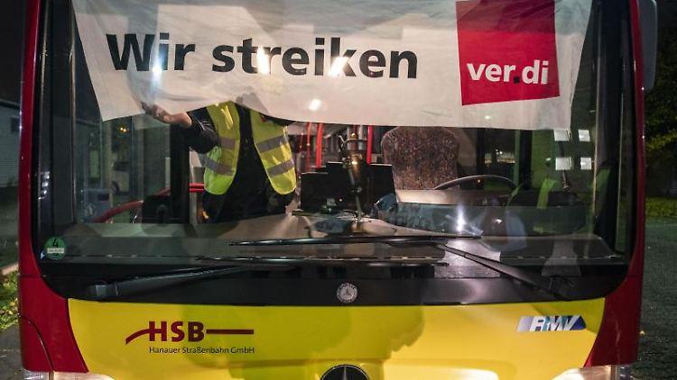 Ein Busfahrer befestigt ein Banner an der Frontscheibe mit der Aufschrift