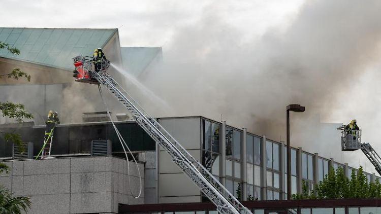 Feuerwehrleute löschen von Drehleitern aus ein Feuer, das in der Rheingoldhalle ausgebrochen war. Foto: Silas Stein/dpa/Archivbild
