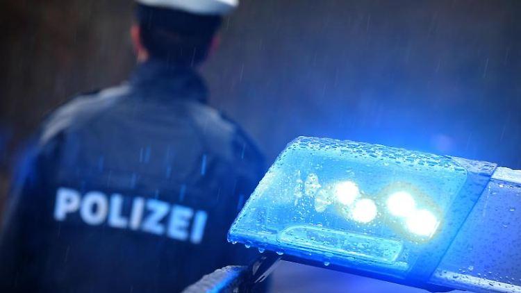 Ein Polizist steht im Regen vor einem Streifenwagen. Foto: Karl-Josef Hildenbrand/dpa/Archivbild