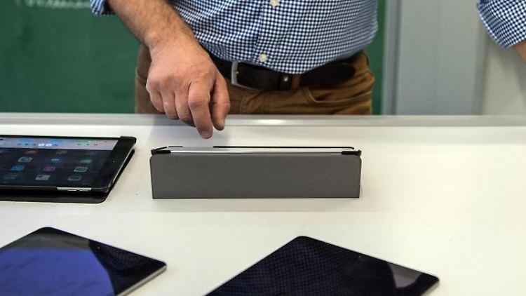 Ein Lehrer bedient in einem Klassenzimmer in einer Schule einen Tabletcomputer. Foto: Wolfram Kastl/dpa/Archivbild