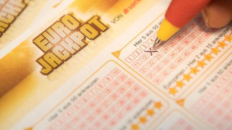 Eine Kundin füllt einen Eurojackpot-Lotterieschein aus. Foto: Fabian Sommer/dpa