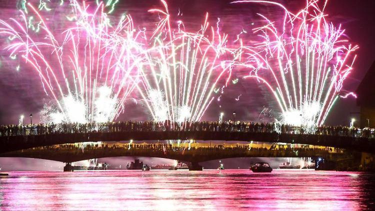 Menschen verfolgen von zwei über den Rhein führenden Brücken aus das Feuerwerk des Seenachtfestes. Foto: Felix Kästle/dpa/Archivbild