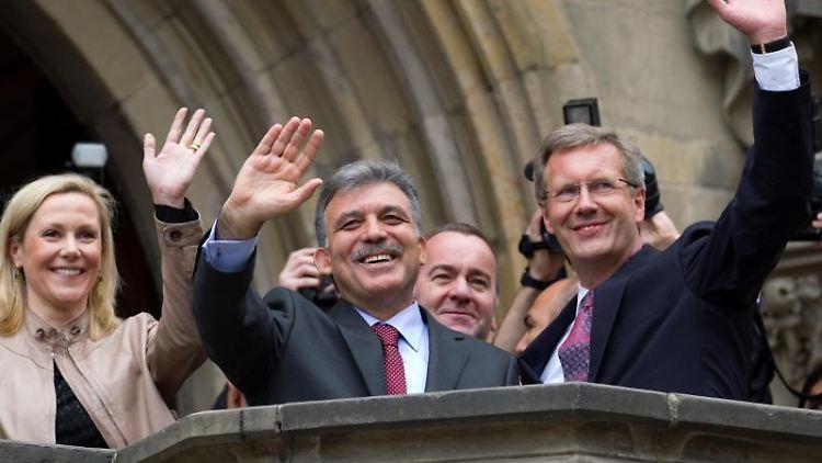 Der damalige Bundespräsident Christian Wulff (r) und seine Frau Bettina (l) winken. Foto: Friso Gentsch/dpa