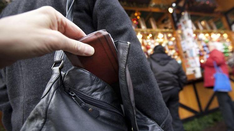 Ein Mann zieht einer Besucherin die Geldbörse aus der Handtasche. Foto: Frank Rumpenhorst/dpa/Archivbild