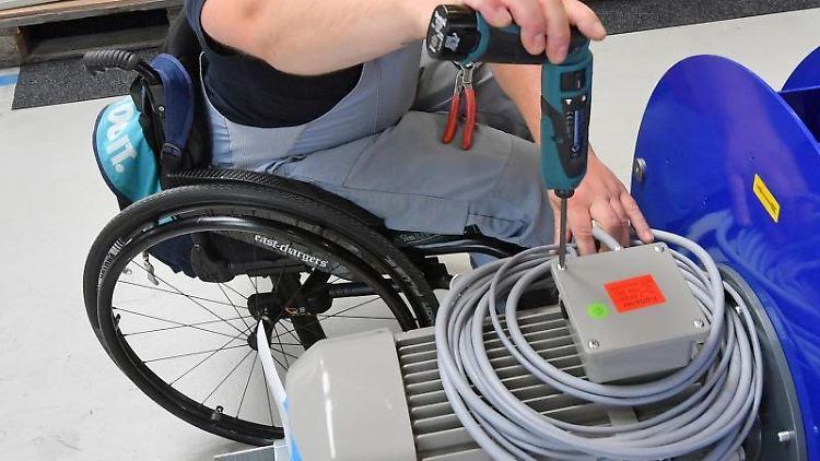 An einem Arbeitsplatz für Motorklemmen arbeitet ein Mitarbeiter im Rollstuhl. Foto: Hendrik Schmidt/zb/dpa/Archivbild