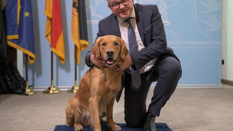 Guido Wolf (CDU), Justizminister von Baden-Württemberg, sitzt neben dem Therapiebegleithund Watson. Foto: Sebastian Gollnow/dpa