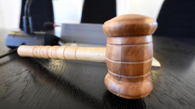 Auf einer Richterbank liegt ein Richterhammer aus Holz. Foto: Uli Deck/dpa