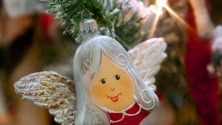 Weihnachtsschmuck hängt an einem Zweig eines Weihnachtsbaums. Foto: Hendrik Schmidt/zb/dpa