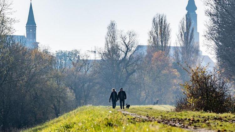 Spaziergänger sind auf einem Donaudamm in Straubing unterwegs. Foto: Armin Weigel/dpa/Archivbild