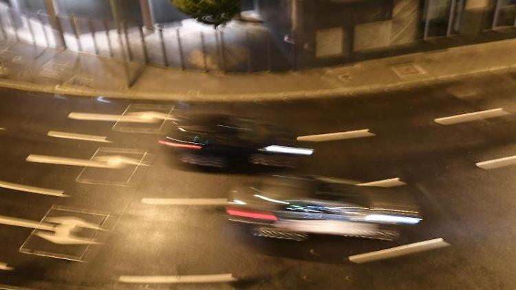 Autos am Abend auf einer Straße mit Straßenmarkierungen und Abbiegepfeilen. Foto: Jens Kalaene/zb/dpa/Symbolbild