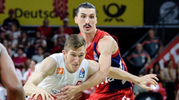 Thomas Joseph Bray von Vechta (l) und Nihad Djedovic von München kämpfen um den Ball. Foto: Matthias Balk/dpa/Archivbild
