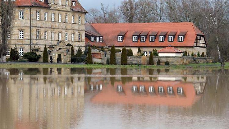 Die Seniorenresidenz Schloss Gleusdorf spiegelt sich in einer überfluteten Wiese. Foto: David-Wolfgang Ebener/dpa/Archivbild