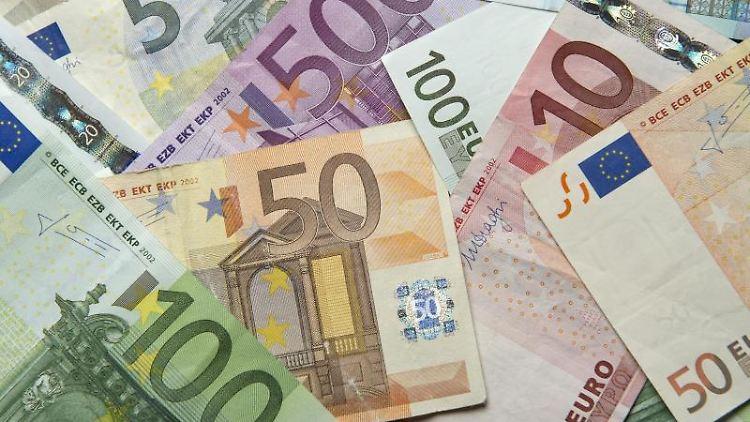 Zahlreiche Euro-Banknoten liegen auf einem Tisch. Foto: Daniel Reinhardt/dpa/Archivbild