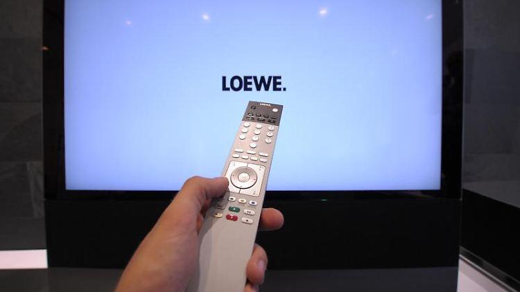 Mit einer Fernbedienung wird im Showroom der Loewe-Firmenzentrale ein Flachbildfernseher bedient. Foto: David-Wolfgang Ebener/dpa/Archivbild