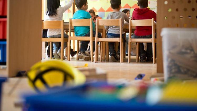 Kindergartenkinder sitzen an einem Tisch in einer Kindertagesstätte. Foto: Daniel Naupold/Archiv