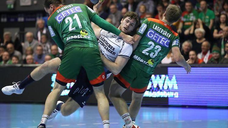 Die Magdeburger E. Schmidt (l) und A. Lagergren (r) spielen gegen den Flensburger J. Golla (M). Foto: Ronny Hartmann/dpa-Zentralbild/dpa