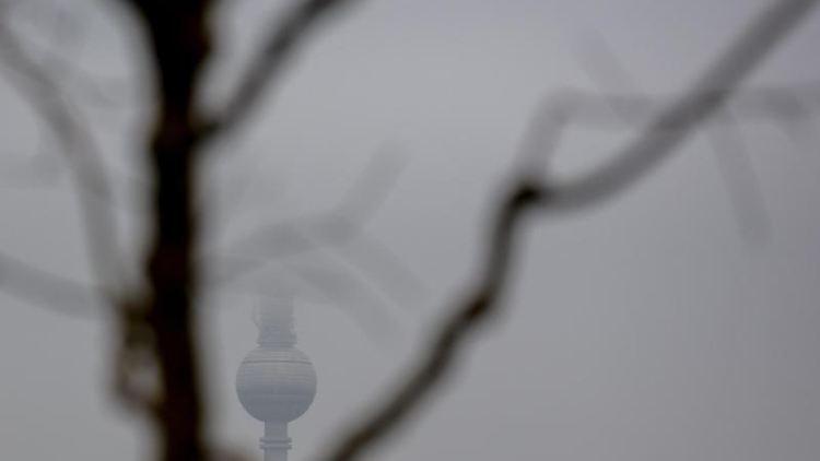 Der halb von Wolken verdeckte Berliner Fernsehturm ist hinter einem laubfreien Baum zu sehen. Foto: Christoph Soeder/dpa
