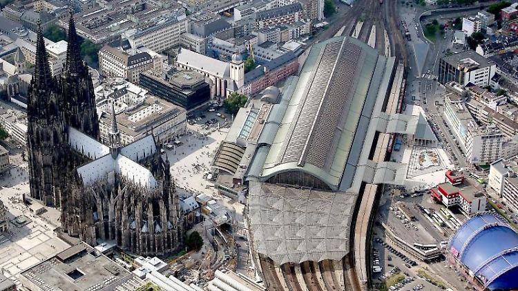 Der Dom (l) und der Hauptbahnhof (r) in Köln sind zu sehen. Foto: Oliver Berg/dpa/Archivbild