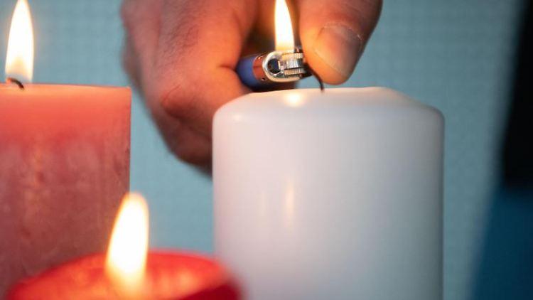 Ein Mann zündet eine Kerze an. Foto: Marijan Murat/dpa
