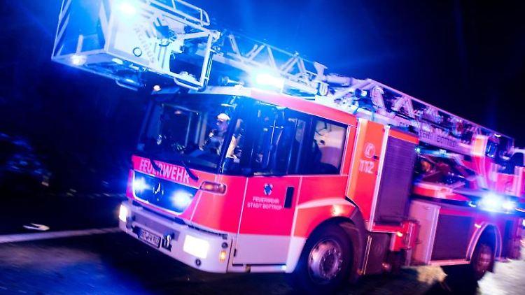 Ein Drehleiterwagen der Feuerwehr fährt mit Blaulicht an einer Unfallstelle vorbei. Foto: Marcel Kusch/dpa