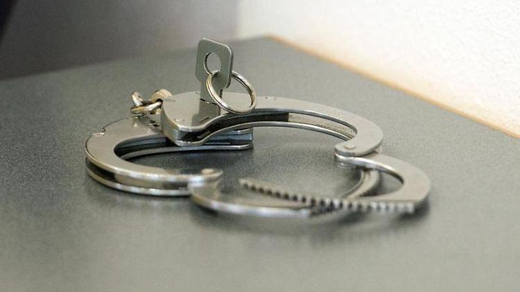 Handschellen liegen auf einem Tisch. Foto: Armin Weigel/dpa/Archivbild