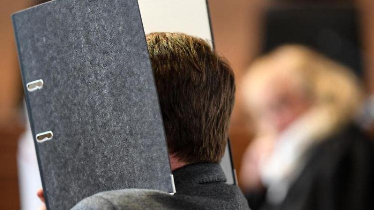 Ein wegen Kindesmissbrauchs angeklagter Soldat sitzt im Gerichtssaal und versteckt sein Gesicht. Foto: Patrick Seeger/dpa/Archivbild