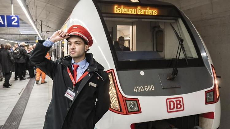Ein Bahnbediensteter steht vor einem S-Bahn-Zug bei der Inbetriebnahme der neuen S-Bahn-Station Gateway Gardens. Foto: Frank Rumpenhorst/dpa