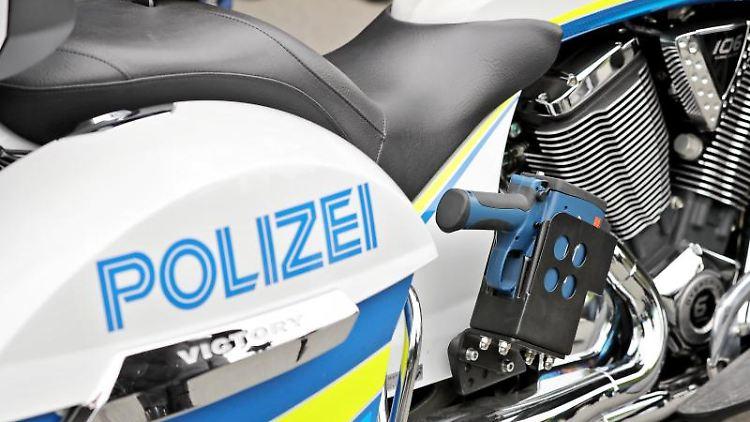Eine Laserpistole hängt an einem Polizeimotorrad