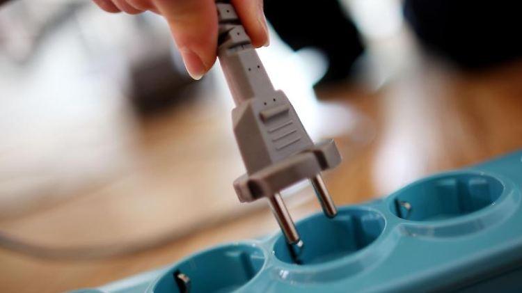 Ein Stecker wird in die Steckdose gesteckt. Foto: Oliver Berg/dpa/Archivbild