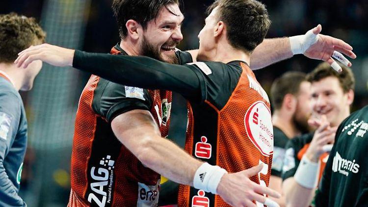 Hannovers Evgeni Pevnov (l) und Hannovers Ivan Martinovic freuen sich über den Sieg. Foto: Uwe Anspach/dpa