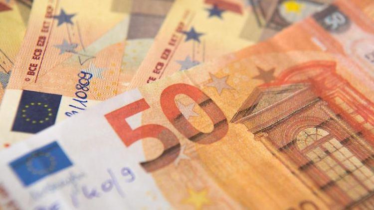 Gefälschte 50-Euro Banknoten liegen auf einem Stapel. Foto: Fabian Sommer/dpa/Archivbild