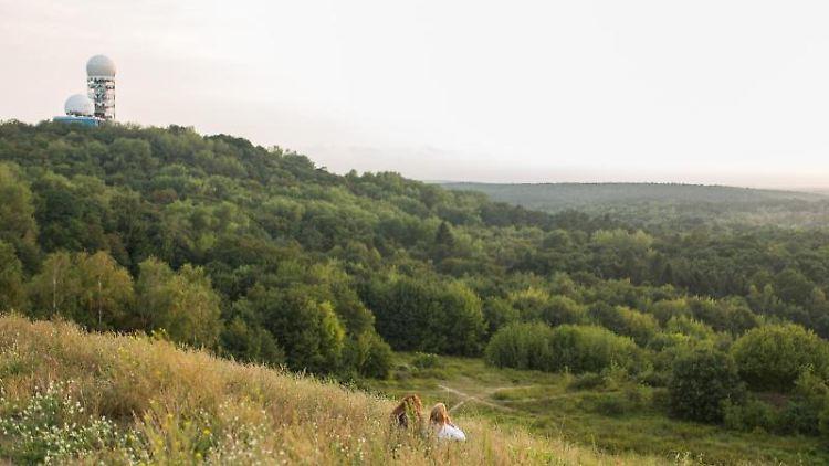Zwei junge Frauen genießen die Aussicht auf den Forst Grunewald und den Teufelsberg. Foto: Lukas Schulze/dpa/Archivbild