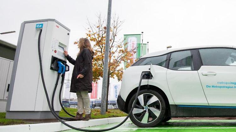 Eine Frau Lädt ein Elektroauto an einer Ladesäule. Foto: Daniel Bockwoldt/dpa/Archivbild