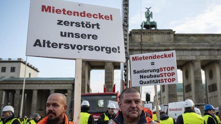 Demonstranten vor Brandenburger Tor mit einem Schild: