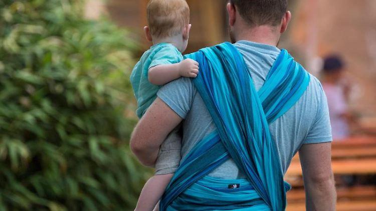 Ein Vater hält ein Baby auf dem Arm. Foto: Monika Skolimowska/zb/dpa/Archivbild