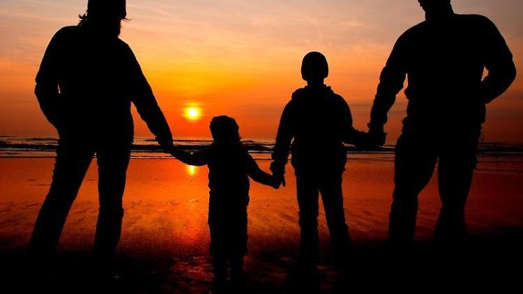 Eine Familie schaut sich einen Sonnenuntergang an. Foto: Patrick Pleul/dpa-Zentralbild/dpa/Archivbild