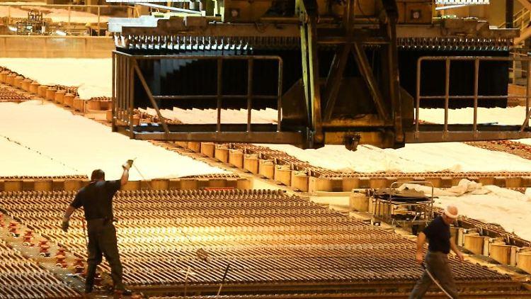 Kupferplatten werden von Arbeitern in ein Elektrolysebad getaucht. Foto: Bodo Marks/dpa/Archivbild