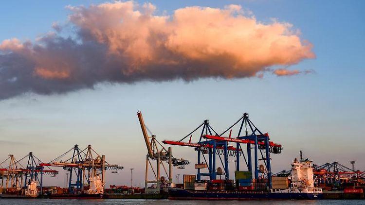 Containerschiffe werden im Hafen im Licht der untergehenden Sonne abgefertigt. Foto: Axel Heimken/dpa/Archivbild