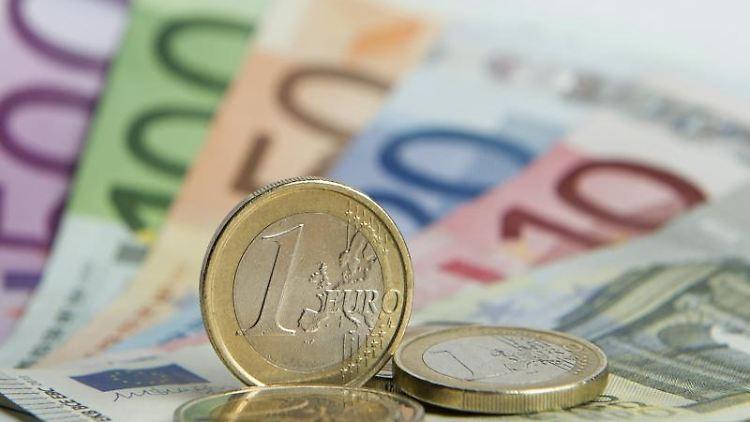 Euro Münzen liegen auf Euro-Banknoten. Foto: Daniel Reinhardt/dpa/Archivbild