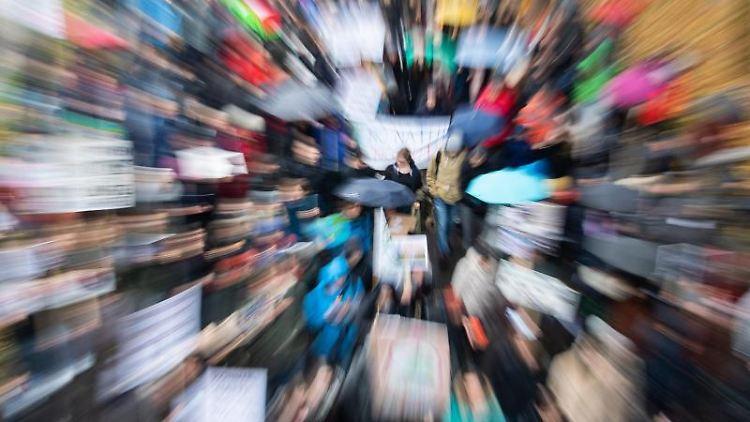Demonstranten von Fridays for Future laufen auf einer Straße und halten Plakate in die Luft. Foto: Tom Weller/dpa/Archiv