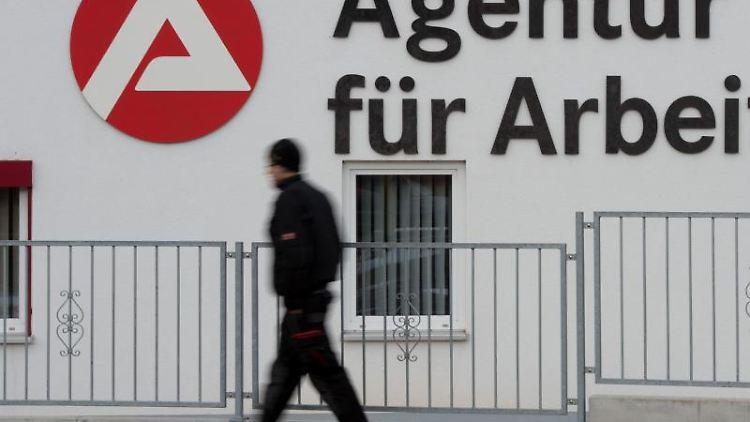 Ein Passant geht an dem Logo der Agentur für Arbeit vorbei. Foto: Sebastian Kahnert/zb/dpa/Archivbild