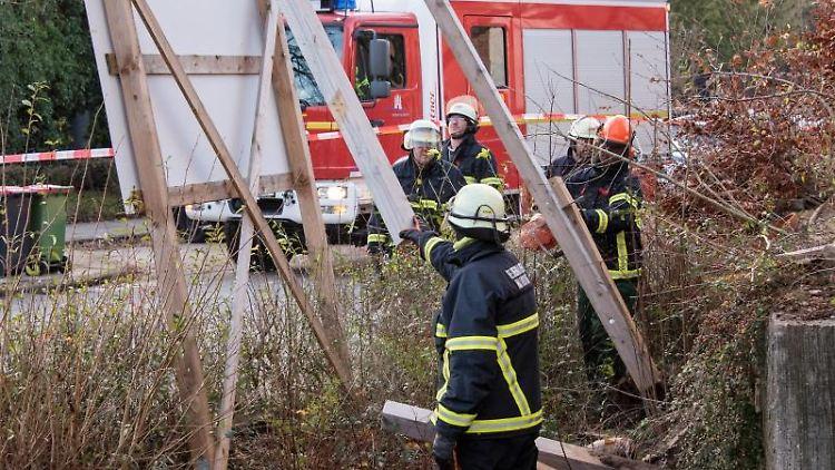 Feuerwehrleute zersägen großes Schild an Baustelle, das drohte, vom Wind umgeweht zu werden. Foto: Daniel Bockwoldt/dpa