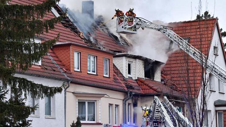 Feuerwehrleute bekämpfen einen Wohnhausbrand am Rande der Innenstadt. Foto: Martin Schutt/dpa-Zentralbild/dpa