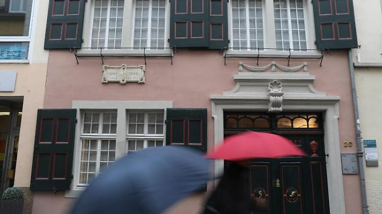 Touristen gehen am Beethoven-Haus vorbei. Foto: Oliver Berg/dpa